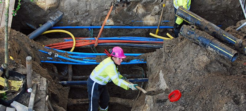 Utility female worker digging around a trench with her shovel  in the street of Amsterdam to install a new electric cable and optical fibre.